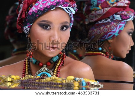 Tan Skin Female Model make skin color like African style with accessory and color fabric, studio lighting, concept in mirror around and reflection herself