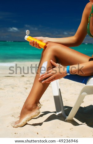 Tan woman applying sun protection lotion - stock photo