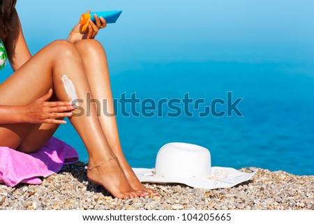 Tan woman applying sunscreen on her legs - stock photo