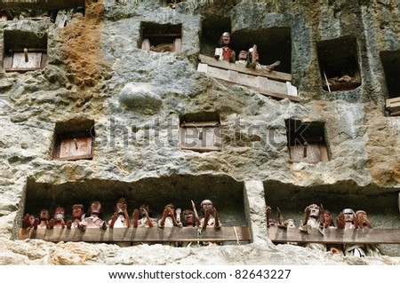 Tana Toraja - Londa, is a very extensive burial cave at the base of a massive cliff face.The entrance to the cave is guarded by a balcony of tau tau. Sulawesi - stock photo