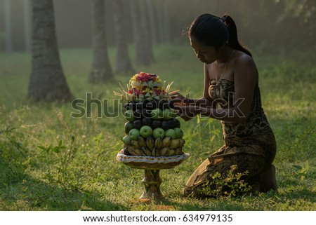 Tanah Embet village, West Lombok, Indonesia - April 23, 2017 : Girl reorganizing her hindu offering for in the morning