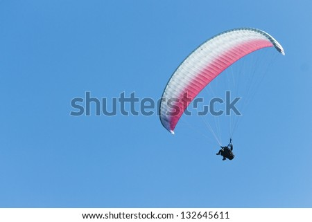 Tandem paragliders on bright blue sky - stock photo