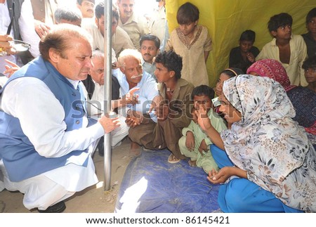 TANDO ADAM, PAKISTAN - OCT 07: Muslim League-N President, Nawaz Sharif talks with flood affectees in a relief camp during his visits on October 07, 2011in Tando Adam.