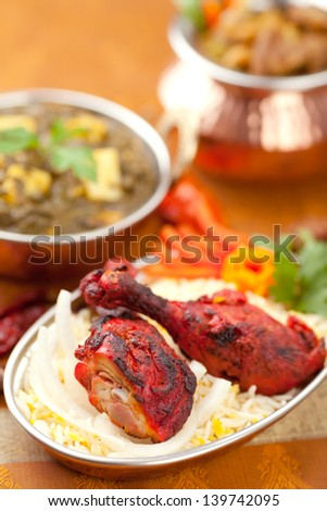 Tandoori chicken in the foreground with Palak Paneer and a bowl of curry in the background. - stock photo