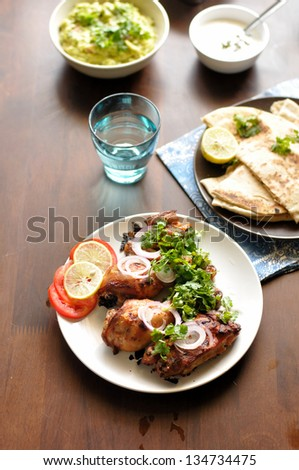 ... Chicken Legs served on top of a naan bread with salad - stock photo