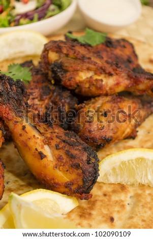 Tandoori chicken legs served on top of a naan bread, with salad, raita and lemon wedges. - stock photo