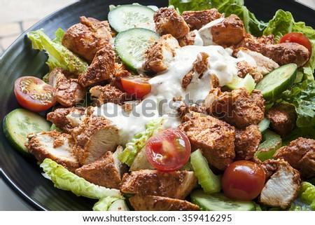 Tandoori chicken salad on black plate. - stock photo