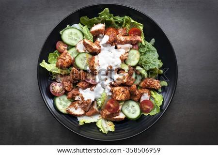 Tandoori chicken salad, overhead view on black slate. - stock photo