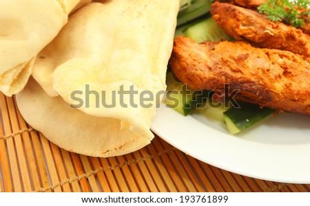 Tandoori chicken with Tortilla Wrap Bread on bamboo mat background - stock photo