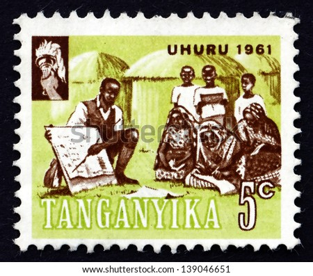 TANGANYIKA - CIRCA 1961: a stamp printed in Tanganyika shows Teacher Instructing Villagers, circa 1961 - stock photo