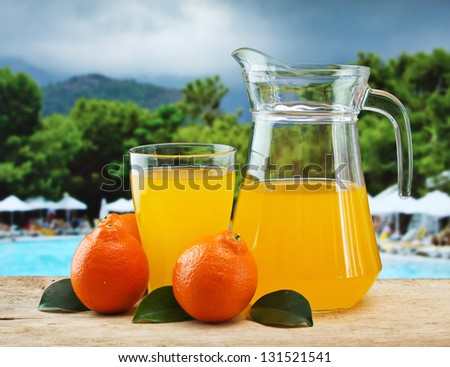 tangerine and juice on a beach table - stock photo