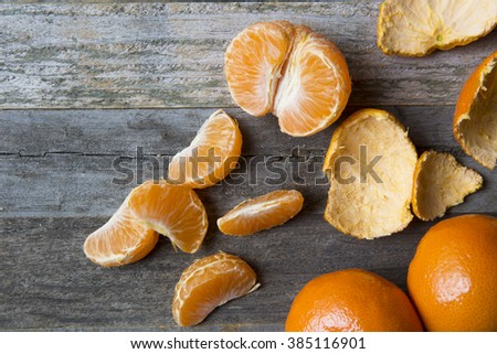 Tangerine sections and peels on old wooden table. - stock photo