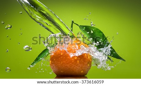 Tangerine with green leaves and water splash on green background. Header for website - stock photo
