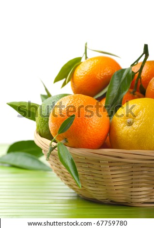 Tangerines and lemon  in a basket on a white background