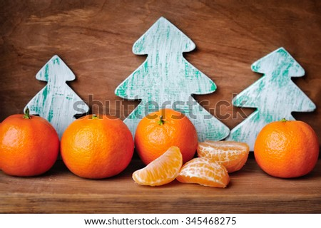 Tangerines and wooden christmas trees on old wooden background - stock photo