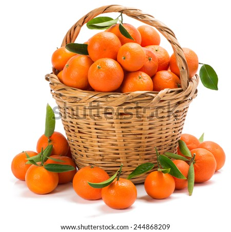 tangerines with green leaves in a basket with handle, some on the surface in the foreground isolated on white - stock photo