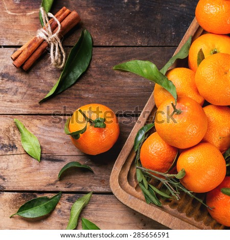 Tangerines with leaves and cinnamon stick on old wooden table. Top view. Square image, selective focus - stock photo