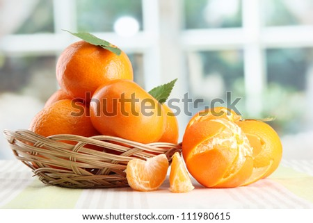 tangerines with leaves in a beautiful basket, on table on window background - stock photo