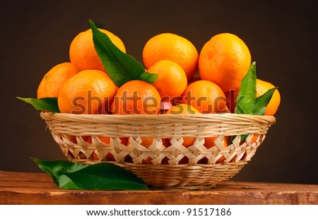 tangerines with leaves in a beautiful basket on wooden table on brown background - stock photo