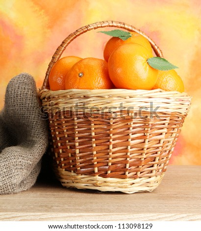 tangerines with leaves in a beautiful basket, on wooden table on orange background - stock photo