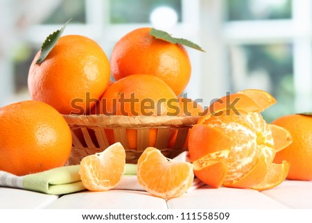 tangerines with leaves in a beautiful basket, on wooden table on window background - stock photo