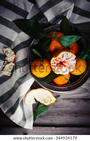 Tangerines with leaves on rustic wooden background - stock photo