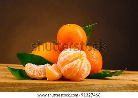 tangerines with leaves on wooden table on brown background - stock photo
