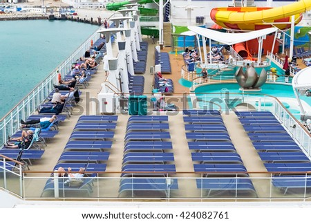 TANGIER, AFRICA - Feb. 26, 2016: Passengers resting on cruise ship.  Tourists on deck of a luxury cruise liner against coastline of Morocco , image for travel tourism concept