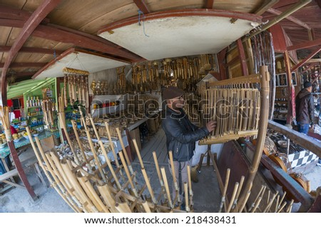 TANGKUBAN PERAHU, BANDUNG, WEST JAVA, INDONESIA - SEPTEMBER 15, 2014: Fisheye view of unidentified man plays traditional musical instrument 'angklung' in Tangkuban Perahu, Indonesia. - stock photo