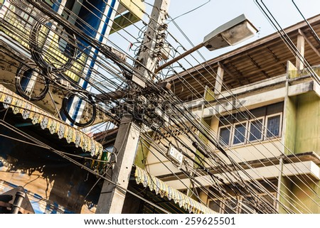 Tangled and messy electrical cables in Bangkok city - stock photo