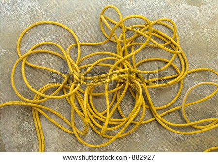 Tangled and worn industrial power extension cable. - stock photo