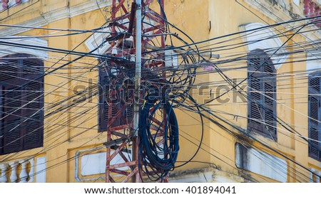 Tangled mess of overhead power lines - stock photo
