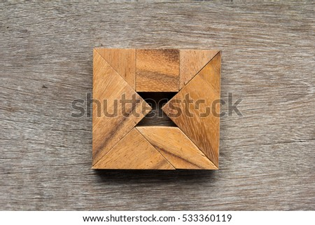 Tangram puzzle as square with hourglass inside shape on old wood background