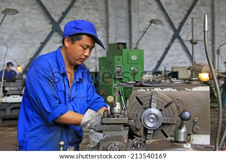 TANGSHAN CITY - JUNE 20: worker working in the machine tool in the production workshop, on June 20, 2014, Tangshan city, Hebei Province, China