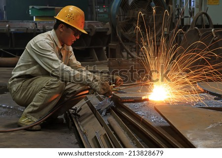 TANGSHAN - JUNE 20: Workers cutting the steel plate in a steel plant, on June 20, 2014, Tangshan city, Hebei Province, China