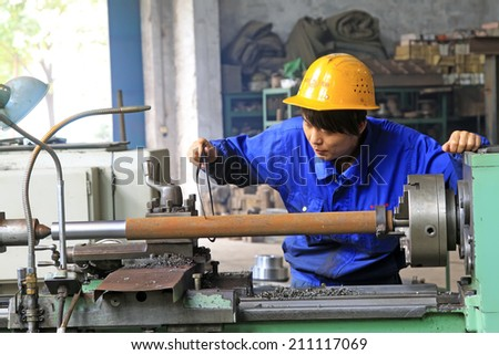 TANGSHAN - JUNE 19: young workers on machine tool in the workshop, on June 19, 2014, Tangshan city, Hebei Province, China