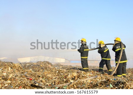 "TANGSHAN - NOVEMBER 20: The words ""Hebei fire"" and ""tangshan fire"" on the clothes, the fireman at the scene of the fire, November 20, 2013, tangshan city, hebei province, China."