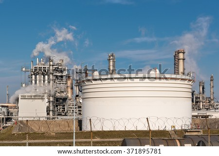 tank in front of an oil refinery with smoking chimneys against blue sky - stock photo