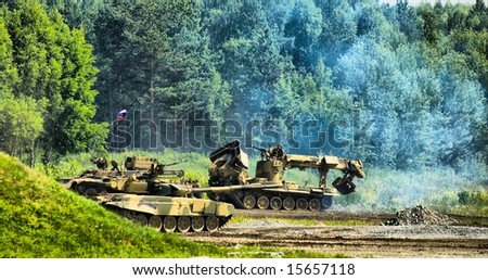 Tank T-80, engineering vehicle moving through field and forest - stock photo