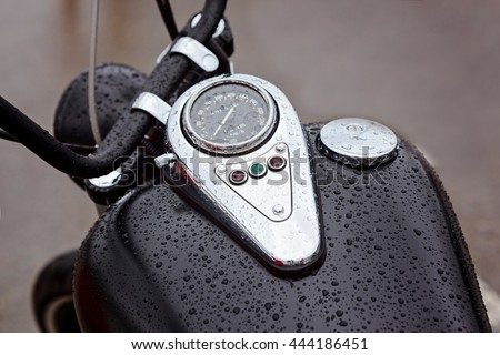 Tank with speedometer with warning lights on a motorbike in the rain