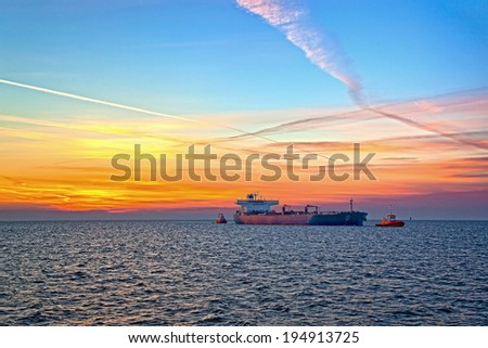 Tanker and tugboat on sea early morning just before sunrise. - stock photo