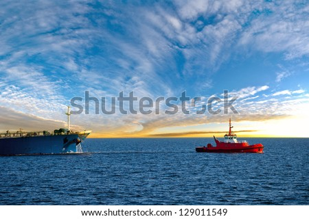 Tanker at sea towed by tug. - stock photo