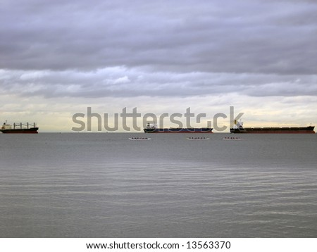 Tanker cargo ships and racing boats on the horizon under an overcast sky - stock photo