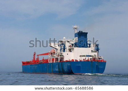 Tanker sailing in the sea with water splashes from engine - stock photo