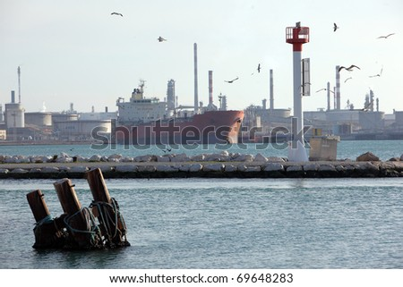 Tanker ship anchored on a dock and being filled of gasoline - stock photo