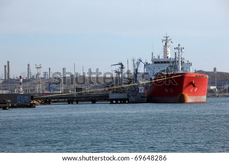 Tanker ship anchored on a dock and being loaded of gasoline - stock photo
