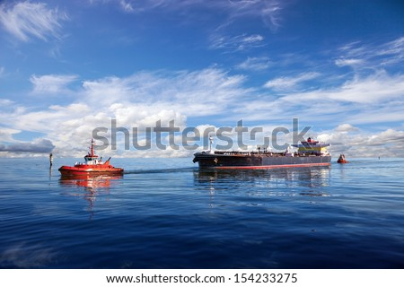 Tanker ship being guided into port by two tugs. - stock photo