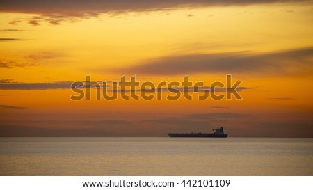Tanker ship in ocean at sunset. - stock photo