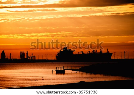 Tanker ship on the background of the rising sun. - stock photo
