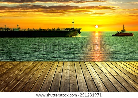 Tanker ship towed by tugboat. View from wooden pier.  - stock photo